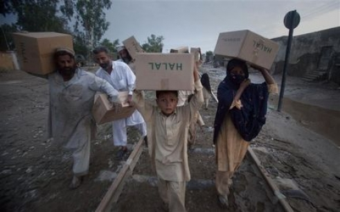 A family carries relief supplies, distributed by the Army, on train tracks back to their homes.