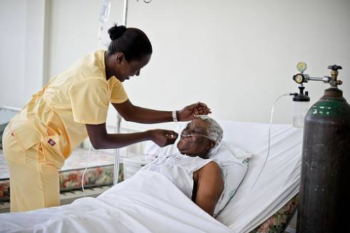 A nurse looks after an older patient in Haiti.