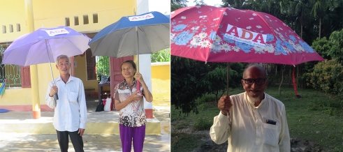 Older people in Vietnam and Bangladesh stand beneath their Age Demands Action umbrellas