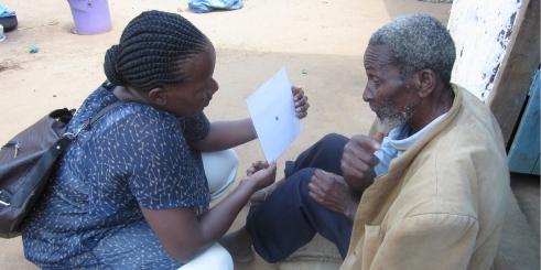 Amillen explains the visual acuity test to an older man in Tanzania (c) Pascale Fritsch/HelpAge International