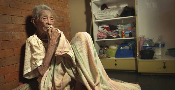 An older woman shelters inside in the aftermath of Typhoon Haiyan (c) Peter Caton/HelpAge International
