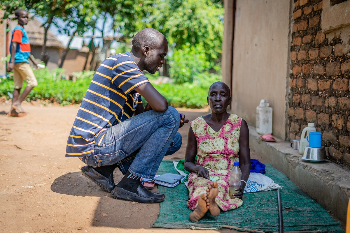 Uganda Reach the Aged Association staff member speaks to blind South Sudanese refugee Atoo in a settlement in Uganda (c) Ben Small/HelpAge International