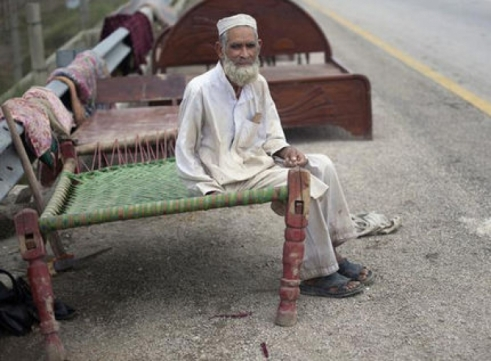Azeem Khan, 70, moved parts of his bedroom onto a nearby tollway to escape flood waters in Mardan, Pakistan.