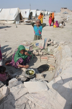 Surrounded by 800 tents in an IDP camp outside Sukkar, a woman cooks spinach on her makeshift cooker