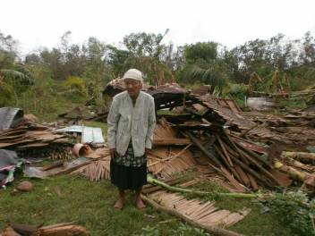 Older woman surveys her wrecked home in the aftermath of Typhoon Haiyan.