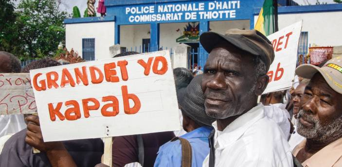 Older campaigner holds a sign in Haiti saying 'seniors can' (c) Joseph Jn-Florley/HelpAge International title=