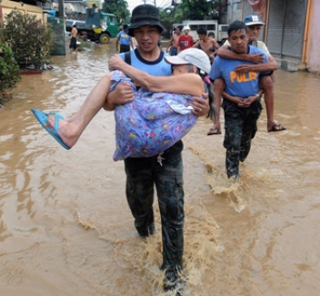 Young people help older people evacuate in Pasig City near Manila during Ketsana. MIKE CLARKE/AFP/Getty Images