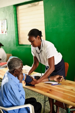 A nurse examines an older patient at a public health centre