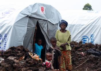 An older displaced woman with her grandchildren outside her tent. (c) Gacheru Maina/HelpAge International