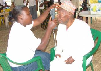 An older man in Tanzania receives an eye test.