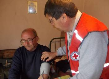 An older man in Serbia has his blood pressure checked. (c) Serbian Red Cross