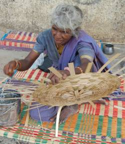 An older woman weaves a basket. (c) Penny Vera-Sanso & CLPHRS