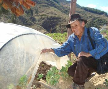 A Bolivian farmer in front of his greenhouse.