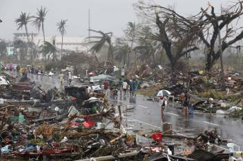Residents walk on a road littered with debris after Super Typhoon Haiyan battered Tacloban city in central Philippines. (c) REUTERS/Erik De Castro Courtesy Trust.org