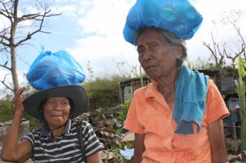 Elisa (84) and Pas (60) walking home with their distribution on their heads. (c) HelpAge International