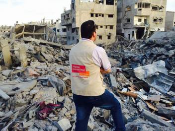 Muaid, HelpAge's Logistics Manager, in front of destroyed houses in Gaza. (c) Nader Al Farra/HelpAge International