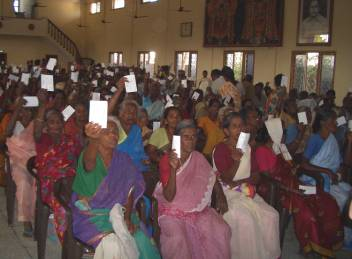 Beneficiaries showing their coupons to receive relief package by HelpAge, at distribution centre in Cuddalore, India