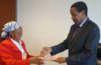 The Permanent Secretary receives Charter 14 from an older leader. (c) John Mwangi/HelpAge International