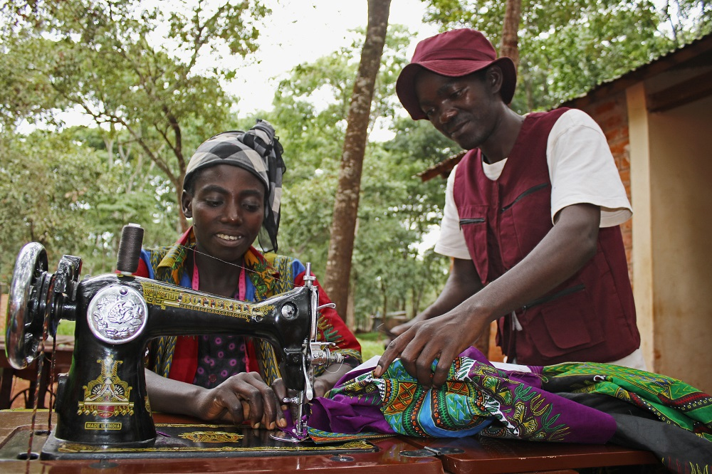 Nadege gets help tailoring from another Burundian refugee in the camps (c) Ben Small/HelpAge International