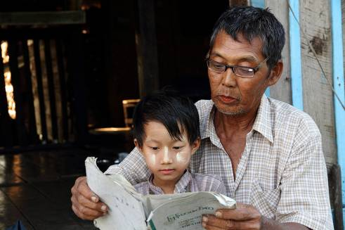 An older man helps his grandson to read.
