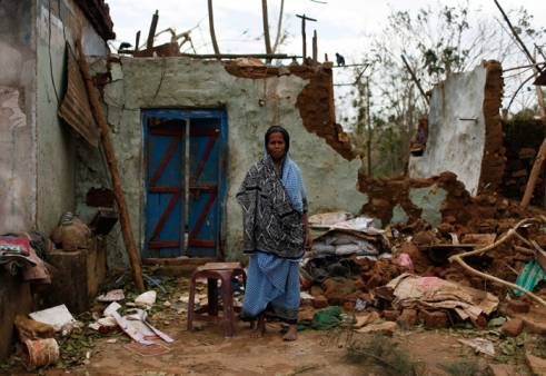 A woman stands outside her damaged house after Cyclone Phailin hit Ganjam district.