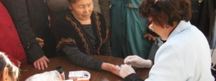 An older woman in Kyrgyzstan is tested for diabetes