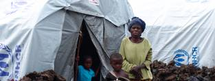 A family in the DRC sit outside their tent in an IDP camp.