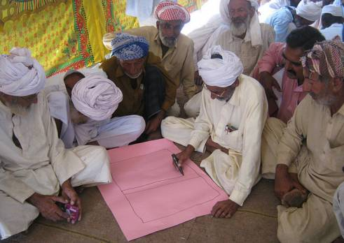 A group of older men in Pakistan take part in a HelpAge disaster risk reduction training session.