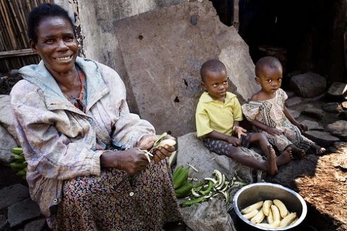 Eliza, 72, cooks a meal for her grandchildren outside her home in Uganda.