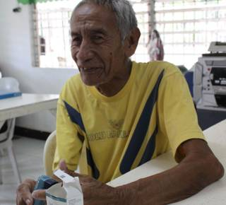 Ely, 70, with his nebuliser that he bought with money from HelpAge and our local partner.