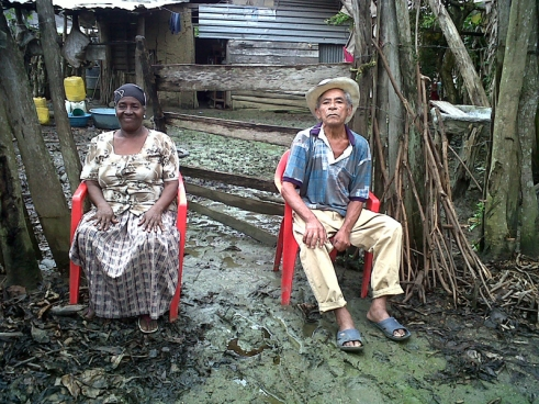 Estebana and Sebastián, sit in the mud outside their house, which was caused by the recent rains.