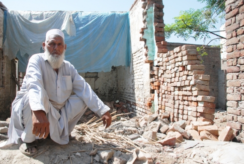 A man sits beside his home damaged by the Pakistan floods
