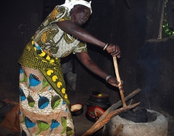 Hadija cooking on a new fuel efficient stove, provided by HelpAge, which produces less smoke.