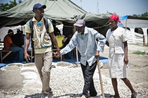 HelpAge staff member in a Haitian camp with older man.