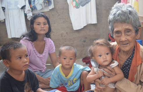 A 99-year-old woman with her granddaugter and great-grandchildren. They have lost their house and are living in an evacuation centre.