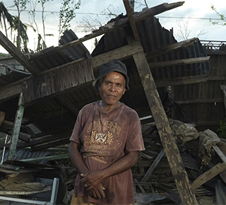 An older man stands in front of the remains of his house in the wake of Typhoon Haiyan (c) Peter Caton/HelpAge International