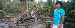 A woman stands in front of her house, which was destroyed by Typhoon Haiyan. (c) COSE