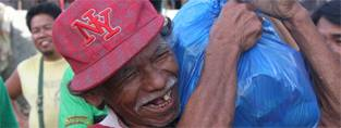 An older man in the Philippines receives his food pack. (c) HelpAge International