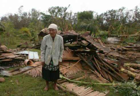 An older woman in Negros Occidental stands in front of her house, which was destroyed by Typhoon Haiyan.