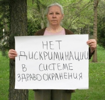 Kyrgyzstan campaigner holds a sign saying 'No discrimination in health care system'
