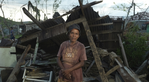 A man stands in front of his house destroyed by Typhoon Haiyan in the Philippines
