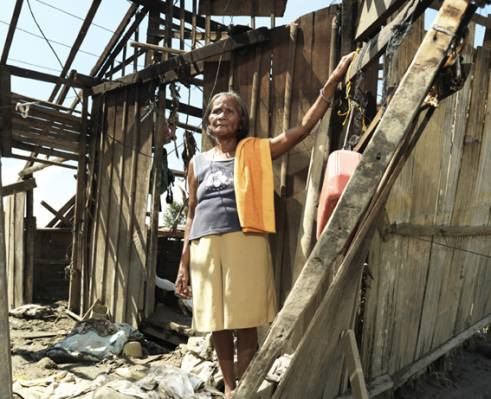 65-year-old widow Luisa surveys the damage to her home after Typhoon Bopha.