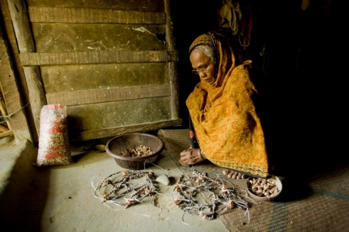 Mabia, 70, from Bangladesh works from morning until night making necklaces.