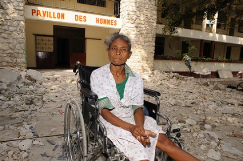 An older woman sits in her wheelchair among the rubble of the municipal nursing home in Port-au-Prince, Haiti.
