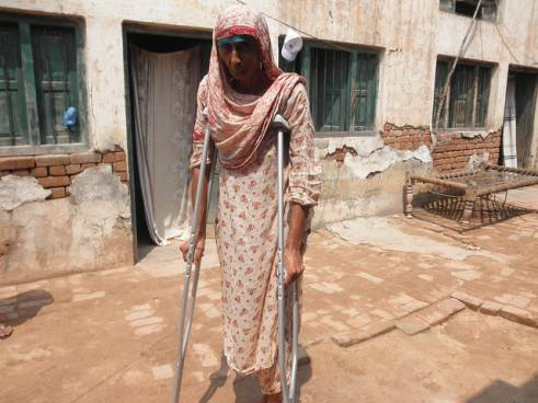 An older woman receives crutches after flooding in Pakistan.