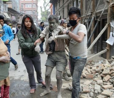 People free a man from the rubble of a destroyed building following a massive earthquake that struck Nepal early on Saturday.