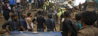 Rescue workers search for bodies as a stretcher is kept ready after an earthquake hit Nepal. (c) REUTERS/Navesh Chitraka