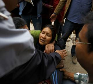 A woman cries as her son is trapped inside a collapsed house after the earthquake. (c) REUTERS/Navesh Chitraka