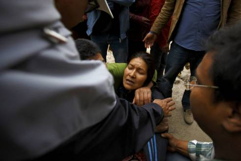 A woman cries as her son is trapped inside a collapsed house after the earthquake.