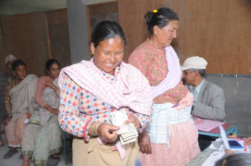 An older woman receiving her cash transfer.